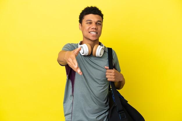 Молодой спортивный афро-американский мужчина со спортивной сумкой на желтом фоне, пожимая руку для заключения хорошей сделки