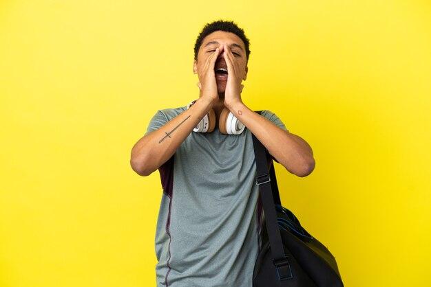 Молодой спортивный афро-американский мужчина со спортивной сумкой, изолированной на желтом фоне, кричит и что-то объявляет
