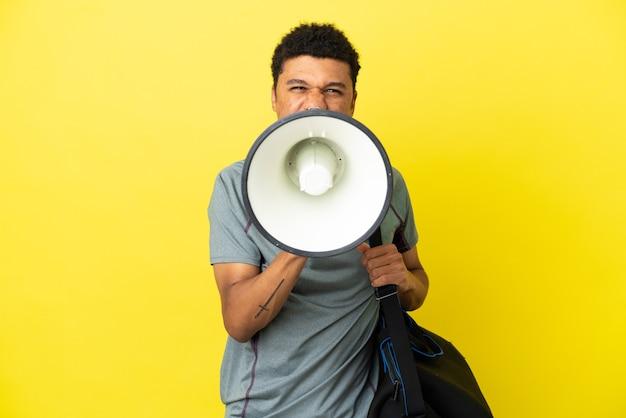 노란색 배경에 격리된 스포츠 가방을 들고 확성기를 통해 외치는 젊은 스포츠 아프리카계 미국인 남자