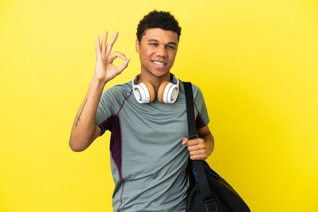 Молодой спортивный афро-американский мужчина со спортивной сумкой, изолированной на желтом фоне, показывает пальцами знак ок