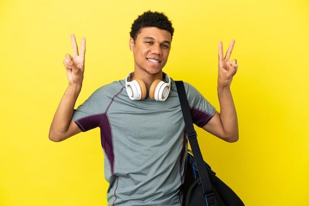 Молодой спортивный афро-американский мужчина со спортивной сумкой, изолированной на желтом фоне, показывает знак победы обеими руками