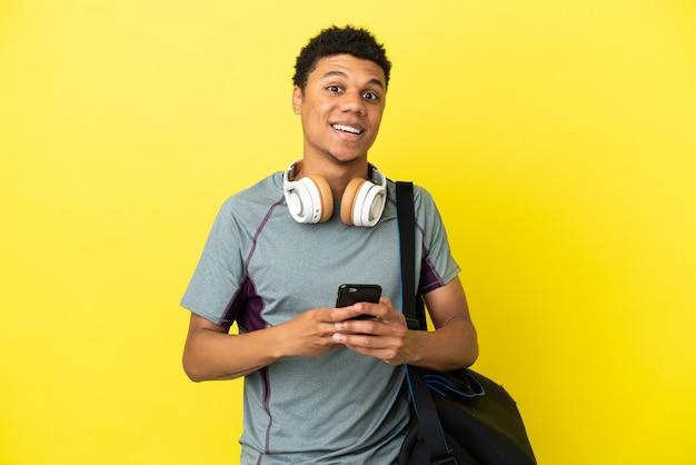 黄色の背景に分離されたスポーツバッグを持つ若いスポーツアフリカ系アメリカ人の男は驚いてメッセージを送信します