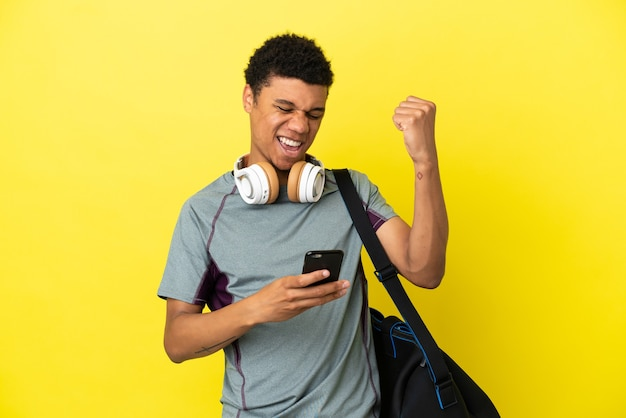 Молодой спортивный афро-американский мужчина со спортивной сумкой на желтом фоне с телефоном в позиции победы
