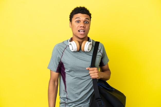 Молодой спортивный афро-американский мужчина со спортивной сумкой на желтом фоне с удивленным выражением лица