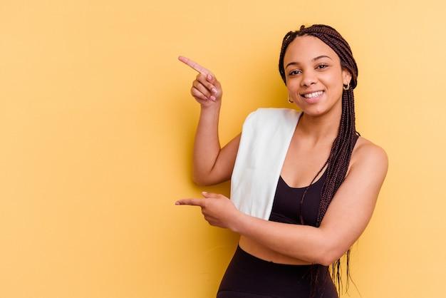 젊은 스포츠 아프리카 계 미국인 여자 수건을 들고 멀리 집게 손가락으로 가리키는 흥분.
