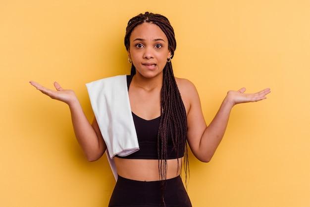 黄色の背景に分離されたタオルを持っている若いスポーツアフリカ系アメリカ人の女性は、コピースペースを保持するために混乱し、疑わしい肩をすくめる肩をすくめます。