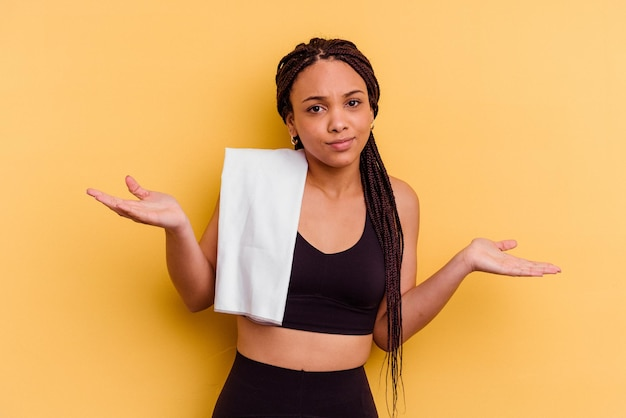 Афро-американская женщина молодой спорт, держащая полотенце, изолированное на желтом фоне, сомневаясь и пожимая плечами в вопросительном жесте.