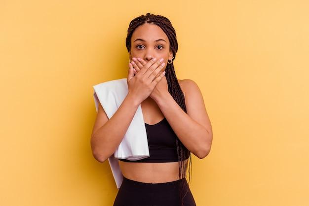 黄色の背景で隔離のタオルを保持している若いスポーツアフリカ系アメリカ人女性は、手で口を覆ってショックを受けました。