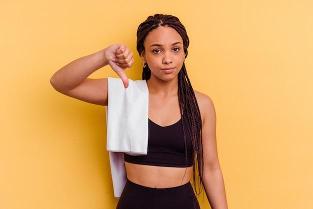 嫌いなジェスチャーを示す黄色の背景に分離されたタオルを持っている若いスポーツアフリカ系アメリカ人女性、親指を下に。不一致の概念。