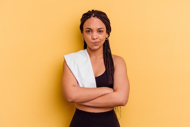 不快な顔をしかめている黄色の壁に隔離されたタオルを保持している若いスポーツアフリカ系アメリカ人の女性は、腕を組んでいます。