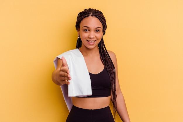 挨拶のジェスチャーで手を伸ばして黄色の壁に分離されたタオルを保持している若いスポーツアフリカ系アメリカ人女性。