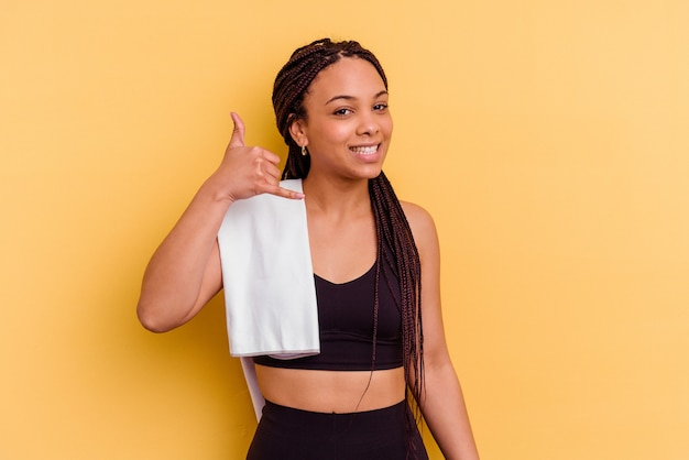 Young sport african american woman holding a towel isolated on yellow wall showing a mobile phone call gesture with fingers.