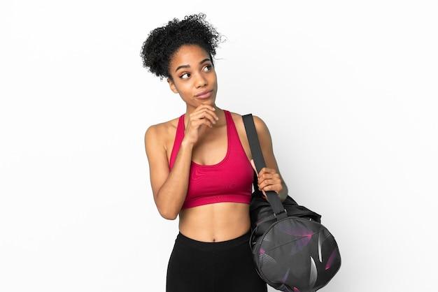 파란색 배경에 격리된 스포츠 가방을 들고 올려다보는 젊은 스포츠 아프리카계 미국인 여성