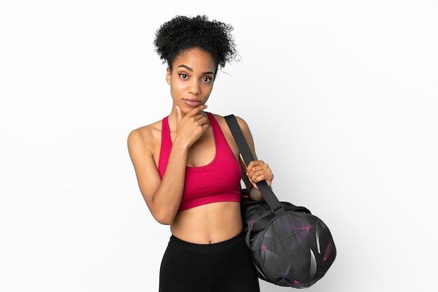 青い背景思考に分離されたスポーツバッグを持つ若いスポーツアフリカ系アメリカ人女性
