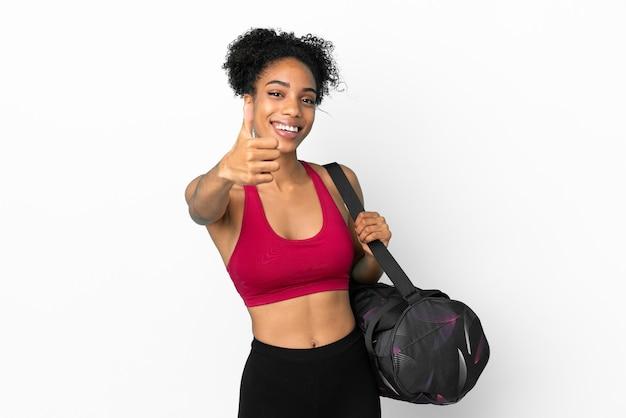 Молодая спортивная афро-американская женщина со спортивной сумкой, изолированной на синем фоне с большими пальцами руки вверх, потому что произошло что-то хорошее