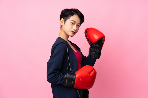 Young sport asian woman over isolated pink wall with boxing gloves