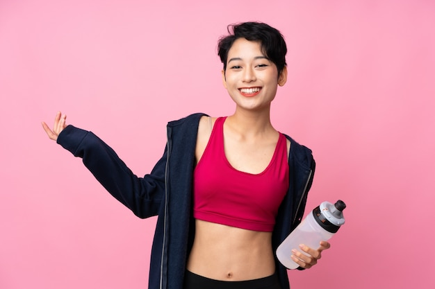 Young sport asian woman over isolated pink wall with sports water bottle