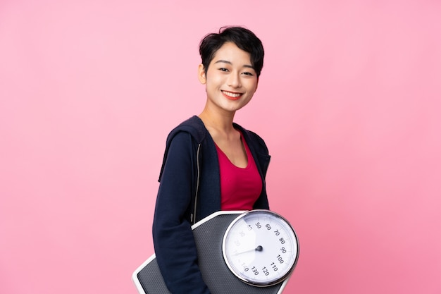 Young sport asian woman over isolated pink wall with weighing machine