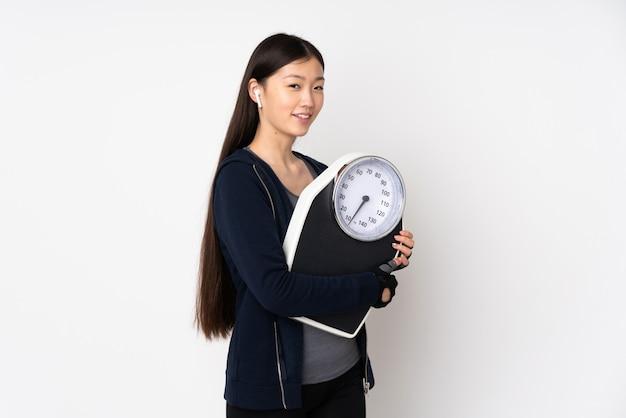 計量機と白い壁に若いスポーツアジアの女性