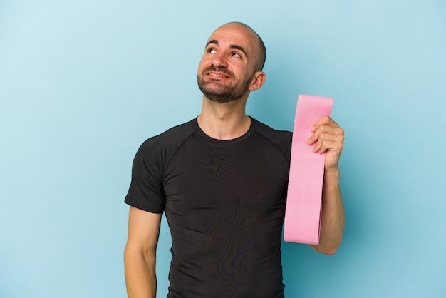 Молодой спортивный лысый мужчина, держащий резинку на синем фоне, мечтающий о достижении целей и задач