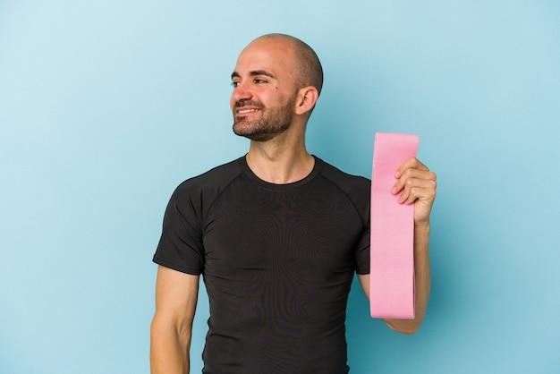Молодой спортивный лысый мужчина, держащий резинку на синем фоне, смотрит в сторону улыбаясь, весело и приятно.