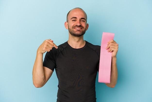 Молодой спортивный лысый мужчина держит резинку, изолированную на синем фоне, человек, указывая рукой на пространство для копирования рубашки, гордый и уверенный