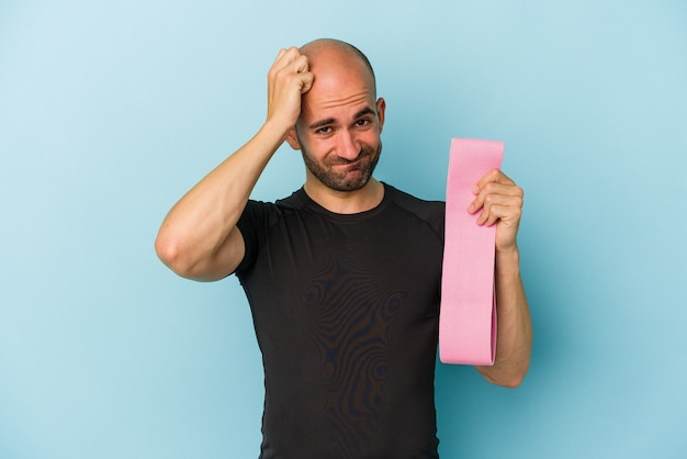 Young sport bald man holding a elastic band isolated on blue background  being shocked, she has remembered important meeting.