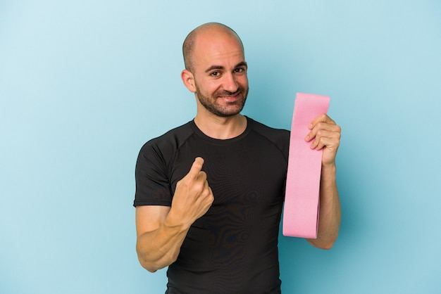 Young sport bald man holding a elastic band isolated on blue background  pointing with finger at you as if inviting come closer.