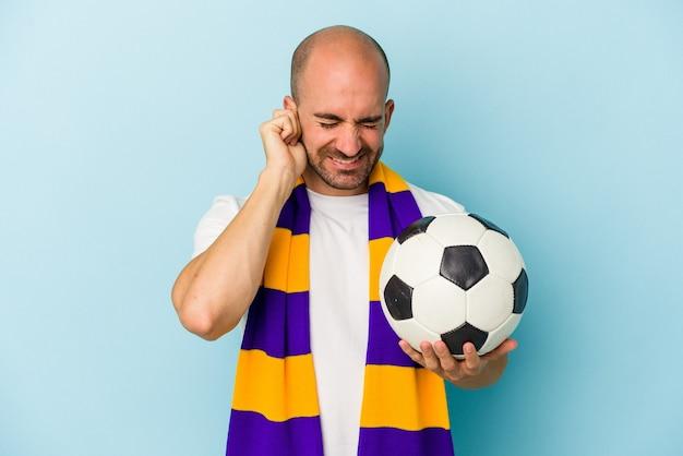 手で耳を覆う青い背景に分離されたスカーフを身に着けている若いスポーツハゲ男。