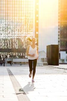 若いスポーツの美しい女の子が街で朝走っています