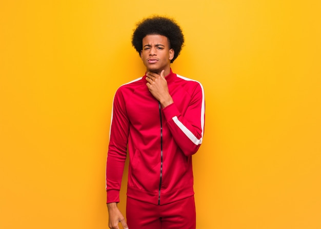 Young sport black man over an orange wall coughing, sick due a virus or infection