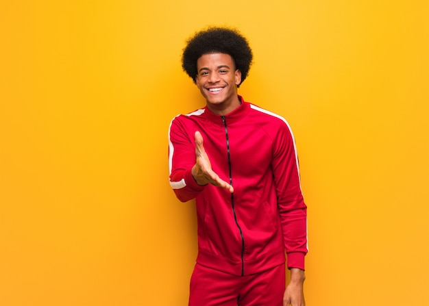 Young sport black man over an orange wall reaching out to greet someone