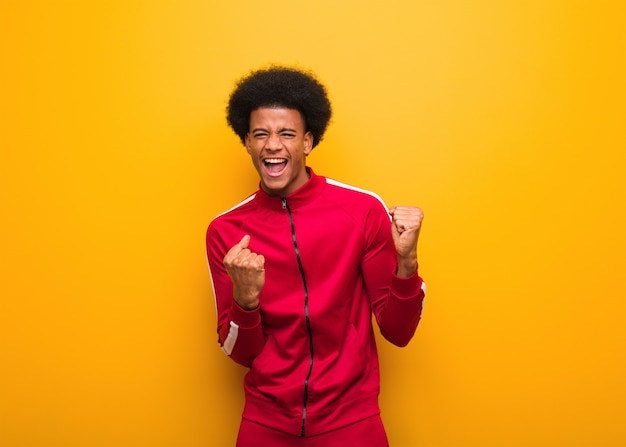 Young sport black man over an orange wall who does not surrender
