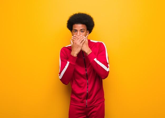 驚いて、ショックを受けたオレンジ色の壁を越えて若いスポーツ黒人男性