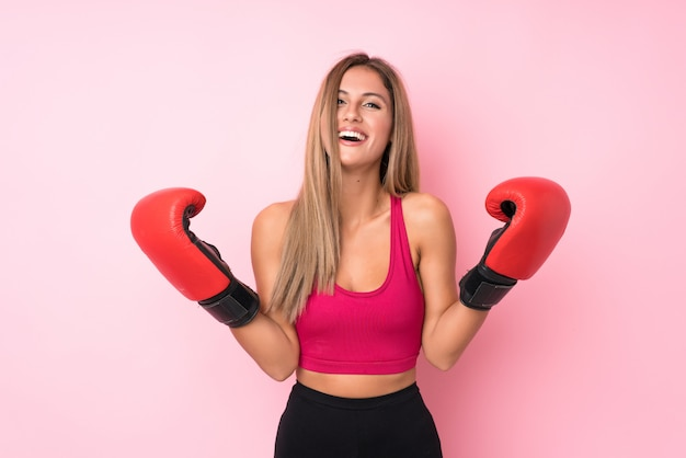 Young sport blonde woman background with boxing gloves