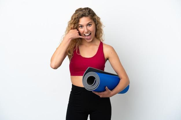 Молодая спортивная белокурая женщина собирается на занятия йогой, удерживая циновку, изолированную на белом фоне, делая жест телефона. перезвони мне знак