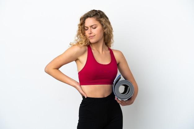 Молодая спортивная блондинка идет на занятия йогой, держа коврик на белом фоне, страдая от боли в спине за то, что приложила усилия
