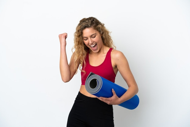Young sport blonde woman going to yoga classes while holding a mat isolated on white background celebrating a victory