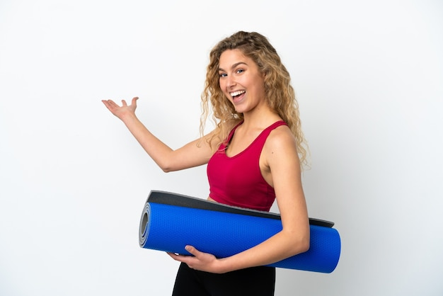 Young sport blonde woman going to yoga classes while holding a mat isolated on white background extending hands to the side for inviting to come
