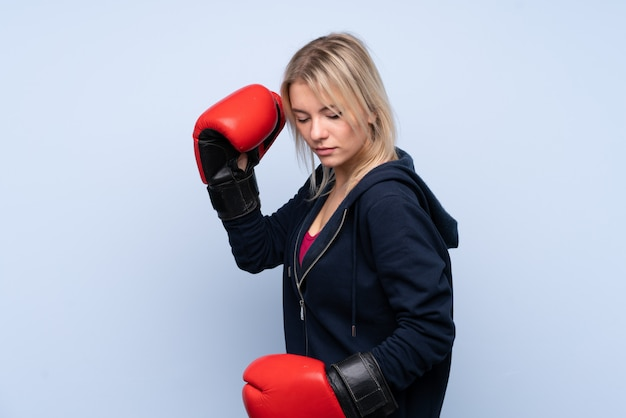 Young sport blonde woman over isolated blue wall with boxing gloves