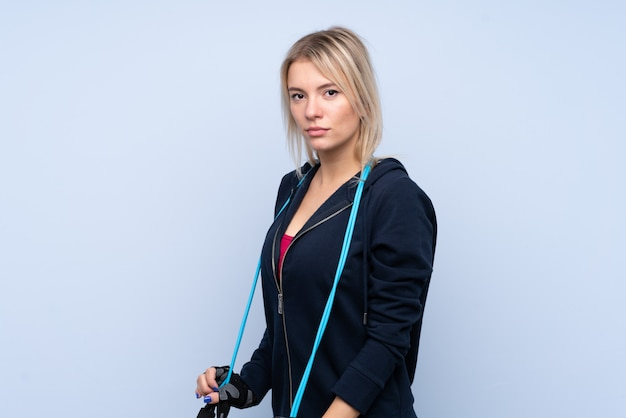 Young sport blonde woman over isolated blue wall with jumping rope