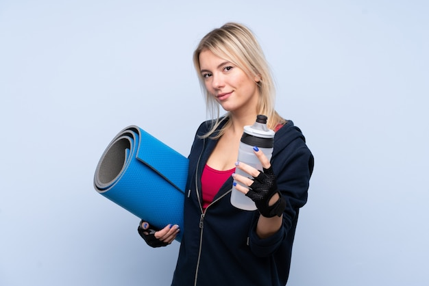 Young sport blonde woman over isolated blue wall with sports water bottle and with a mat