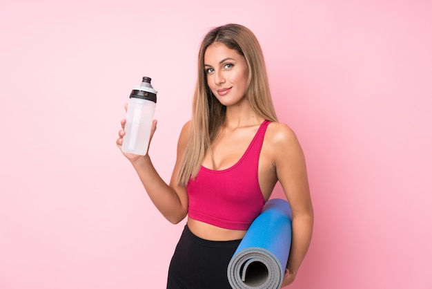 Young sport blonde woman over isolated pink background with sports water bottle and with a mat