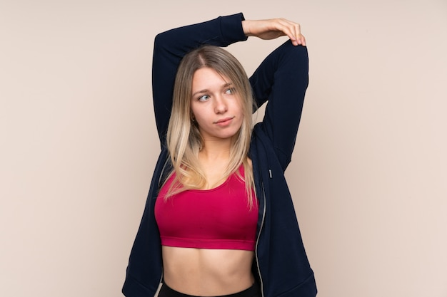 Young sport blonde woman over isolated wall stretching