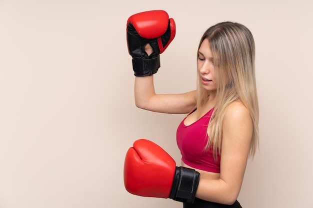 Young sport blonde woman over isolated wall with boxing gloves