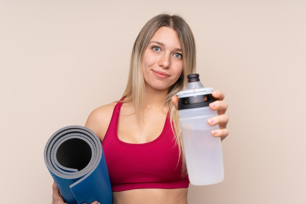 Young sport blonde woman over isolated wall with sports water bottle and with a mat