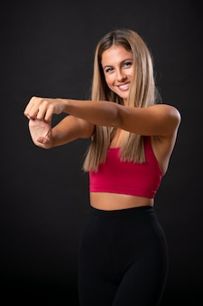 Young sport blonde woman stretching over isolated black