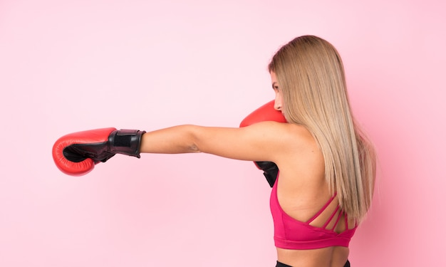 Young sport blonde woman with boxing gloves over isolated pink