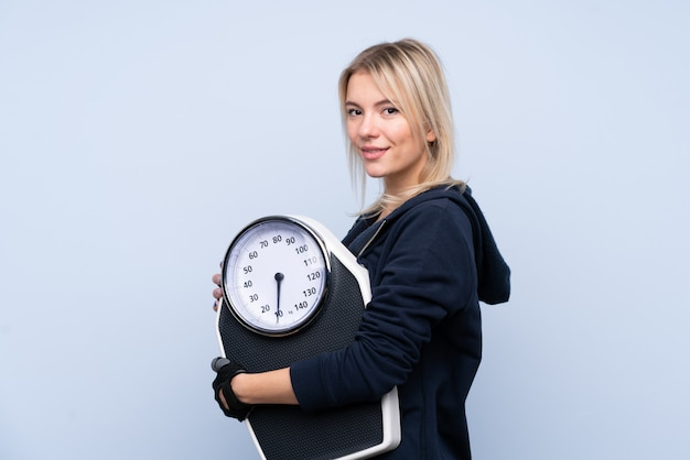 Young sport blonde woman with weighing machine