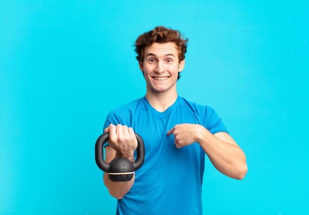 Молодой спортивный мальчик чувствует себя счастливым, удивленным и гордым, указывая на себя взволнованным, изумленным взглядом. гантели